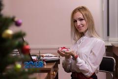 Trabajo femenino de risa en oficina en la Navidad Imagenes de archivo