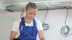Trabajo femenino del constructor del contratista del ingeniero en el edificio de apartamentos almacen de metraje de vídeo