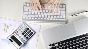 Trabajo femenino del negocio en oficina y email que mecanografía con el ordenador del teclado en el escritorio blanco metrajes