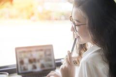 Trabajo femenino en el ordenador portátil en el lugar de trabajo mujer atractiva feliz que usa el ordenador portátil para estudia foto de archivo