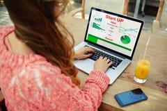 Trabajo femenino joven del empresario con las estadísticas datos y funcionamiento el analizar en su cuaderno foto de archivo