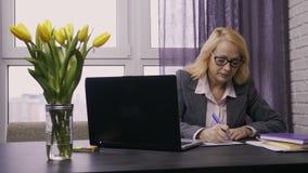 Trabajo femenino mayor en la PC del ordenador portátil en el escritorio almacen de video