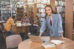 Trabajo femenino positivo con el ordenador portátil Imagen de archivo