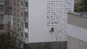 Trabajo a gran altitud Los trabajos del hombre sobre alta subida trabajan el revestimiento, enyesado de la casa El calentarse de  metrajes