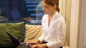 Trabajo hermoso de la muchacha del freelancer sobre el ordenador portátil en café metrajes