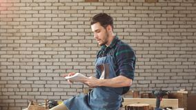 Trabajo hermoso del carpintero en carpintería Él es empresario acertado en su lugar de trabajo almacen de video