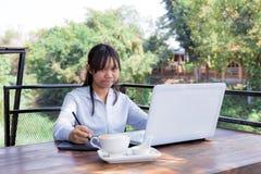 Trabajo independiente adolescente con la pluma del ratón en el ordenador portátil Fotografía de archivo libre de regalías