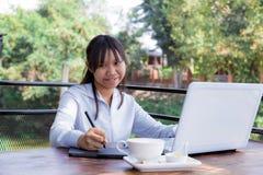 Trabajo independiente adolescente con la pluma del ratón en el ordenador portátil Imagen de archivo libre de regalías