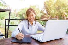 Trabajo independiente adolescente con la pluma del ratón en el ordenador portátil Fotos de archivo libres de regalías