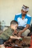 Trabajo infantil en el negocio de Sari Pertiwi Wood Carving, Juga, Bali, Indonesia fotos de archivo