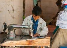 Trabajo infantil, muchacho que cose en cabina en el mercado Imagen de archivo