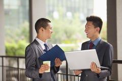 Trabajo joven de dos hombres de negocios al aire libre, mirando uno a Imagenes de archivo