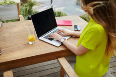 Trabajo joven de la mujer de negocios sobre el texto que mecanografía del netbook durante el desayuno en cafetería moderna Fotos de archivo