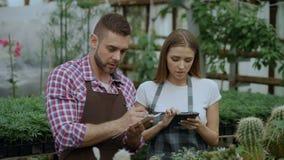 Trabajo joven de los floristas de los pares en centro de jardinería Flores cheking y mujer del hombre atractivo que usa la tablet metrajes