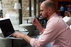 Trabajo joven del empresario sobre el netbook que sostiene la taza de té o de café mientras que él que se sienta en cafetería mod foto de archivo