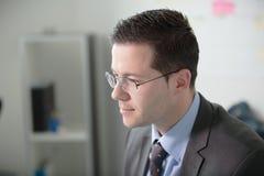 Trabajo joven feliz del hombre de negocios en oficina moderna Hombre de negocios hermoso In Office Bussinesmen reales del economi fotografía de archivo libre de regalías