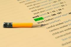 TRABAJO - Las palabras destacan en el libro y el lápiz Foto de archivo libre de regalías