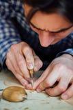 Trabajo más luthier del artesano principal en la creación de un violín trabajo detallado cuidadoso sobre la madera imagen de archivo