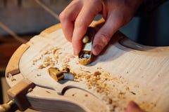 Trabajo más luthier del artesano principal en la creación de un violín trabajo detallado cuidadoso sobre la madera Imagen de archivo libre de regalías