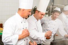 Trabajo masculino del cocinero dos en cocina profesional imagen de archivo libre de regalías