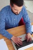Trabajo masculino ocupado en ordenador portátil mientras que se sienta en butaca roja imagen de archivo libre de regalías
