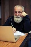 Trabajo mayor barbudo atractivo en su ordenador portátil Foto de archivo libre de regalías