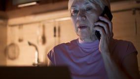 Trabajo mayor de la mujer sobre el ordenador portátil de Ministerio del Interior por la tarde Charla del Freelancer sobre el telé almacen de video