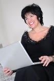 Trabajo mayor de la mujer sobre la computadora portátil Foto de archivo