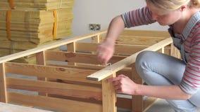 trabajo No-femenino la mujer joven monta los muebles de madera dentro almacen de metraje de vídeo
