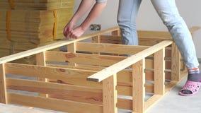 trabajo No-femenino la mujer joven monta los muebles de madera dentro V?deo acelerado metrajes