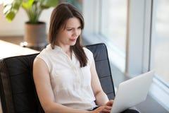 Trabajo ocupado de la mujer acertada en el ordenador portátil que se sienta en silla foto de archivo libre de regalías
