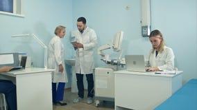 Trabajo ocupado de los médicos en la oficina usando los ordenadores portátiles y la tableta Foto de archivo libre de regalías