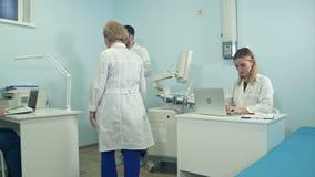 Trabajo ocupado de los médicos en la oficina usando los ordenadores portátiles y la tableta almacen de metraje de vídeo