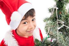 Trabajo ocupado del niño pequeño en el árbol de navidad para la celebración Foto de archivo
