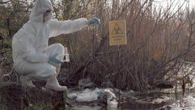 Trabajo peligroso, biólogo del hazmat en la ropa protectora que recoge la muestra infectada de agua en los tubos de ensayo para e almacen de metraje de vídeo