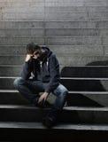 Trabajo perdido sin hogar del hombre joven que se sienta en la depresión en las escaleras de tierra del hormigón de la calle imágenes de archivo libres de regalías