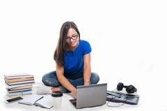 Trabajo que se sienta de la muchacha del estudiante en el ordenador portátil con los libros alrededor Imagen de archivo libre de regalías