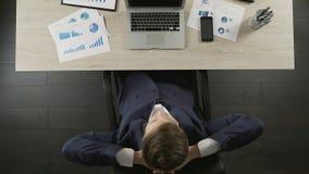Trabajo seguro de sí mismo del acabamiento del hombre de negocios sobre el ordenador portátil y relajación en el lugar de trabajo metrajes