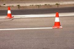 Trabajo sobre el camino Conos de la construcción Trafique el cono, con las rayas blancas y anaranjadas en el asfalto Señales de l foto de archivo libre de regalías