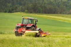 Trabajo sobre una granja agrícola Un tractor rojo corta un prado foto de archivo