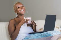 Trabajo sonriente de la mujer afroamericana negra feliz hermosa joven en el ordenador portátil en casa relajado en el sofá del so imagen de archivo