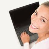 Trabajo sonriente de la mujer del ordenador portátil en la PC del ordenador Fotos de archivo libres de regalías