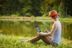 Trabajo/studing de la chica joven en el parque imagen de archivo libre de regalías