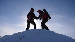 Trabajo y victoria del equipo Los turistas amplían la mano al amigo que sube al top de la colina el equipo de hombres de negocios almacen de video