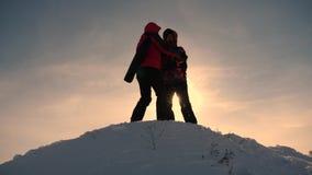 Trabajo y victoria del equipo Los turistas amplían la mano al amigo que sube al top de la colina Escaladores en invierno en la mo metrajes