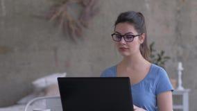 Trabajoadicto femenino en las lentes que mecanografían el texto en el teclado del ordenador portátil y que miran la pantalla du almacen de video