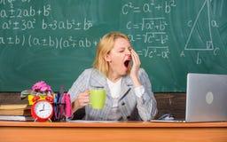 Trabajoadicto soñoliento en el lugar de trabajo La mujer del profesor sienta el fondo de la pizarra de la sala de clase de la tab imágenes de archivo libres de regalías