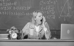 Trabajoadicto soñoliento en el lugar de trabajo La mujer del profesor sienta el fondo de la pizarra de la sala de clase de la tab fotografía de archivo