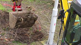 """Trabajos amarillos pequeños de un excavador cerca suelo y raíces cargados del excavador del †constructivo """" metrajes"""