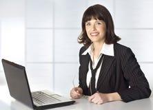 Trabajos con gafas de la mujer de negocios con una computadora portátil Fotografía de archivo libre de regalías